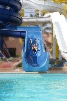 Happy boy on water slide in summer