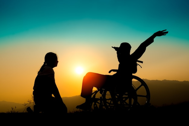 Happy boy in wheelchair and sister on sunset. happy disabled child concept