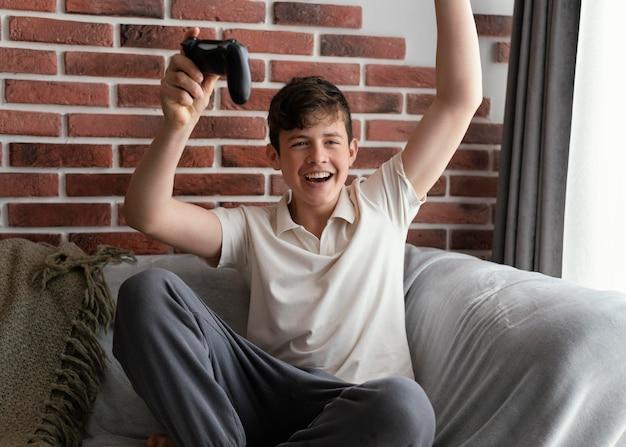 Счастливый мальчик выигрывает видеоигру