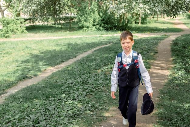 Счастливый мальчик с рюкзаком и кепкой ходит в школу. начало нового учебного года после летних каникул.