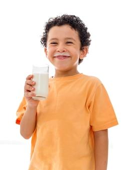 白い背景の上のミルクのガラスを持つ幸せな少年