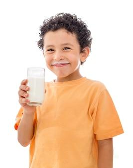 ミルクのガラスを持つ幸せな少年