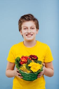 Счастливый мальчик с корзиной цветов в руке в желтой футболке, изолированной на синей стене, копией пространства