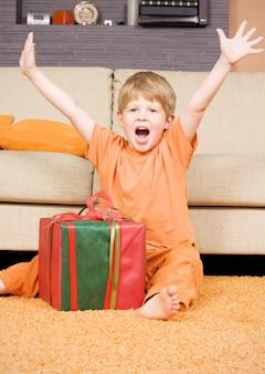 Счастливый мальчик с большой подарочной коробкой