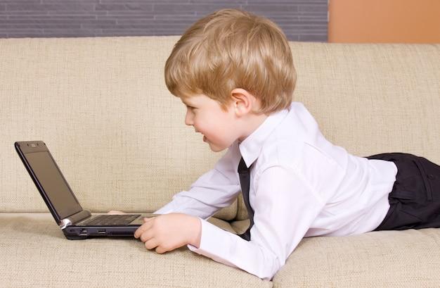 검은 노트북 컴퓨터와 함께 행복 한 소년