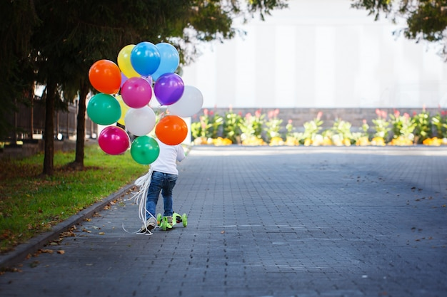 Happy boy with a bunch of colored balloons riding a scooter.