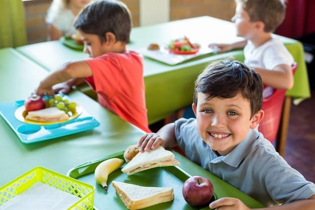 Счастливый мальчик с одноклассниками едят