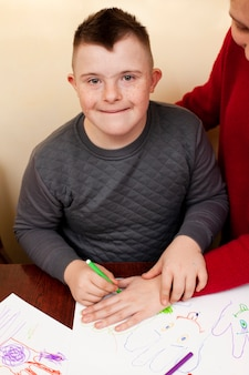 Happy boy with down syndrome drawing