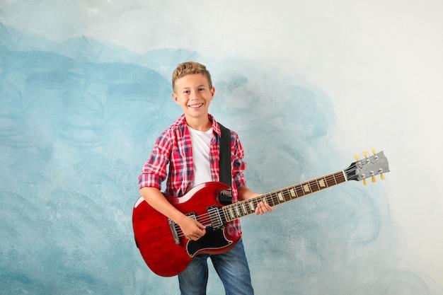 色の背景、テキスト用のスペースのエレクトリックギターと幸せな少年