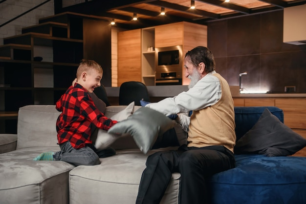 Happy boy with funny modern grandpa fighting with pillows having fun together sitting on comfortable couch at home.