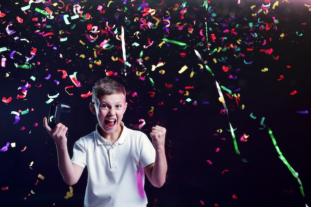 Happy boy with gamepad and flying confetti