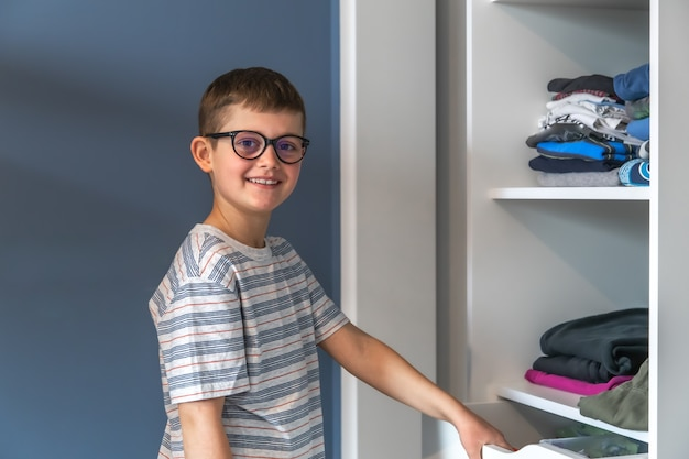 A happy boy with glasses stands near a wardrobe and thinks about what to wear.