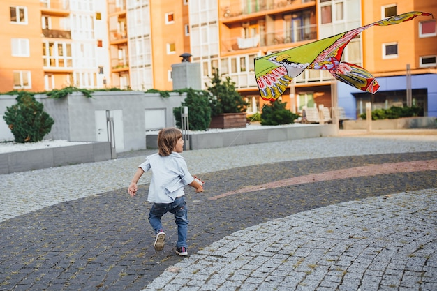 Happy boy with a kite playing on the streets