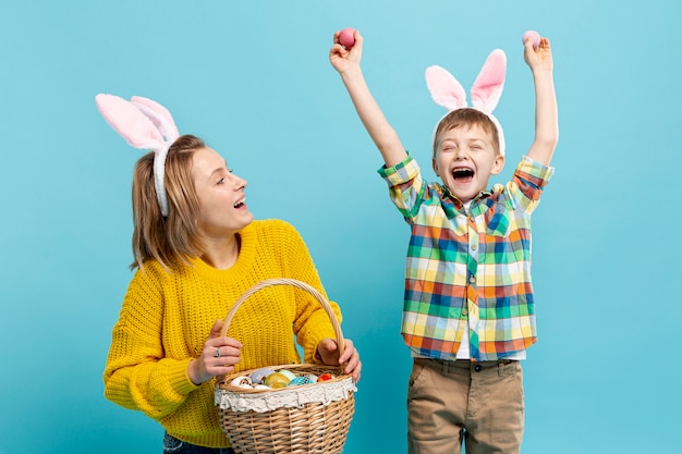 Happy boy with mom holding basket with painted eggs