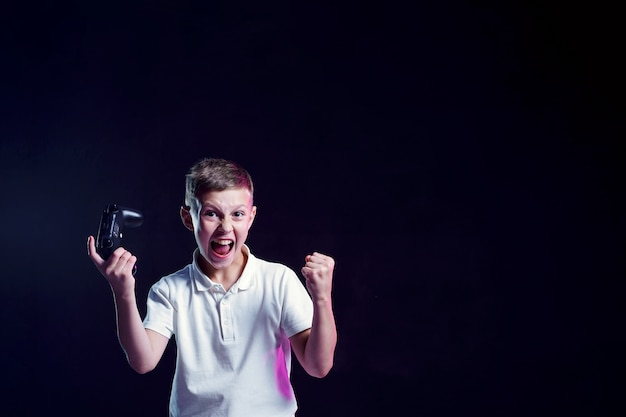 Happy boy with open mouth and joystick shouting for joy after winning in video game on black wall