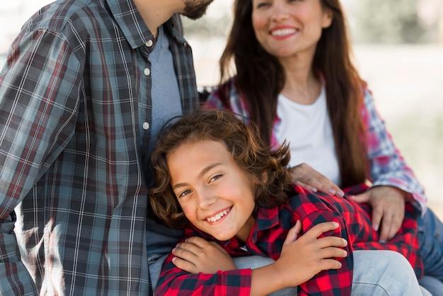 Счастливый мальчик с родителями на открытом воздухе