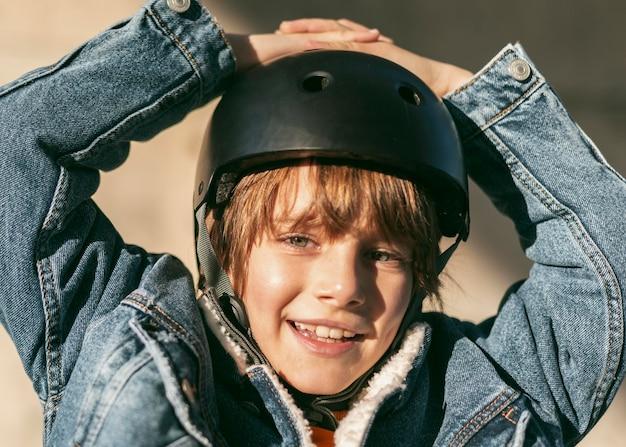 그의 자전거를 타기위한 안전 헬멧을 가진 행복 한 소년