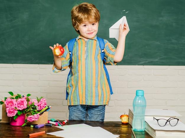教室でランドセルを持つ幸せな少年。小学校の子供。教育と学習。