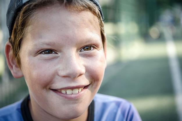 サッカーのクローズアップポートレートをプレイした後の汗まみれの顔を持つ幸せな少年