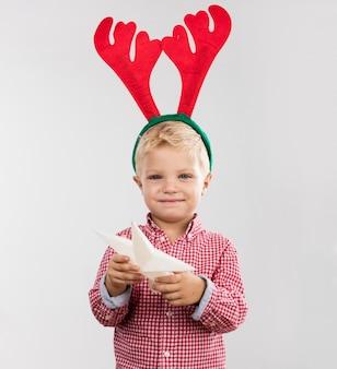 Ragazzo felice con albero stelle e corna di renna