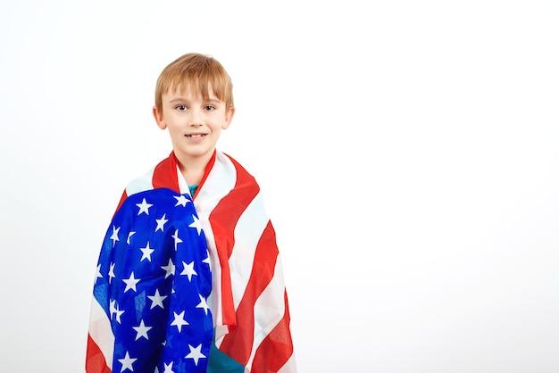 흰색 배경 위에 절연 미국 국기와 함께 행복 한 소년. 행복한 아이는 미국 국기를 보유하고 있습니다.