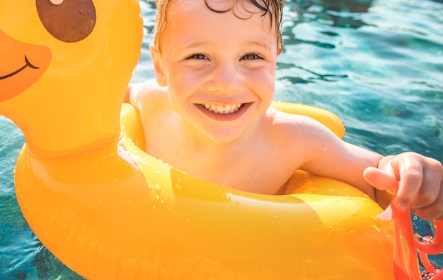 Happy boy and a yellow duck tube in the pool