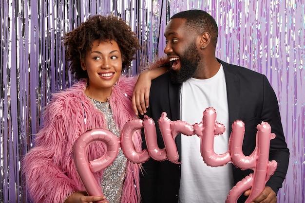 幸せなボーイフレンドとガールフレンドは、パーティーのお祝いの間に写真を作り、ピンクの文字の形をした風船を持って、顔に広い笑顔を持っています