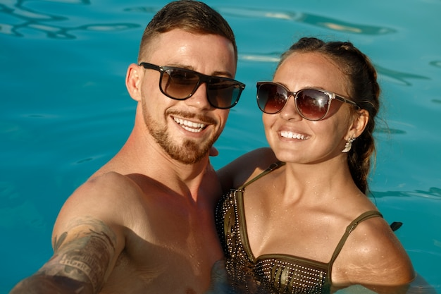 Happy boyfriend and girlfriend taking selfie while resting in the swimming pool