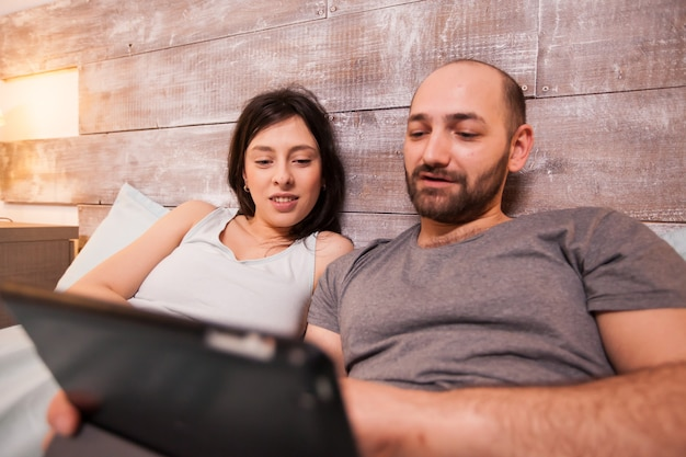 Happy boyfriend and girlfriend wearing pajamas lying in bed browsing on tablet computer.