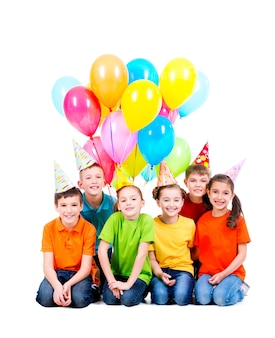 Ragazzi e ragazze felici in cappello del partito con palloncini colorati che si siedono sul pavimento - isolato su bianco