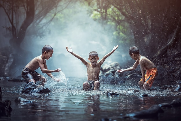 Happy boys has fun playing in the creek, thailand countryside