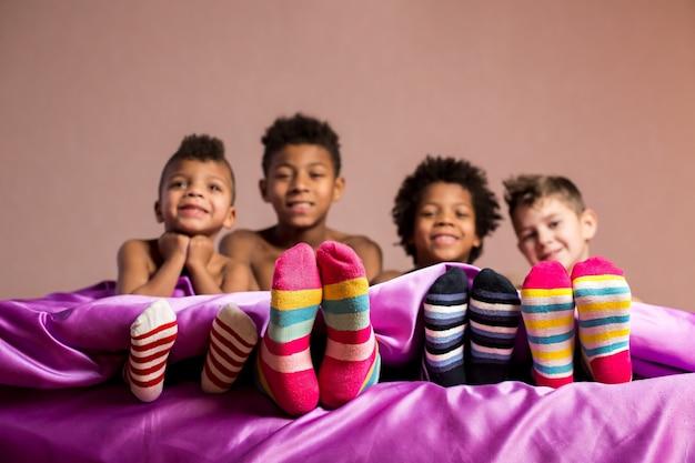 カラフルな靴下で幸せな男の子。ベッドに座っている陽気な男の子。あなたの友情を大切にしなさい。私たちが若い頃。