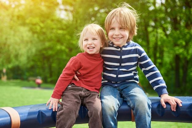 Счастливые мальчики играют на детской площадке в солнечный день