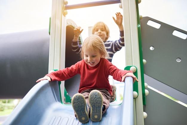 晴れた日に遊び場で遊んで幸せな少年