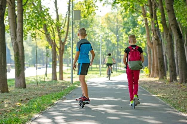 Счастливые мальчики с роликовыми коньками и самокатом, гуляя по дороге в парке, летом