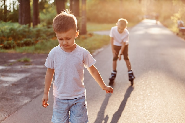 Happy boys with roller skates riding on road at the park, summertime, little boy with concentrated expression learning roller skating with brother, kids wearing casual style attires.