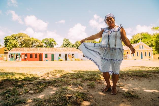 ポルトセグロの歴史的中心部で、ウンバンダ宗教の伝統的なバイーアの衣装を着た幸せなブラジル人女性