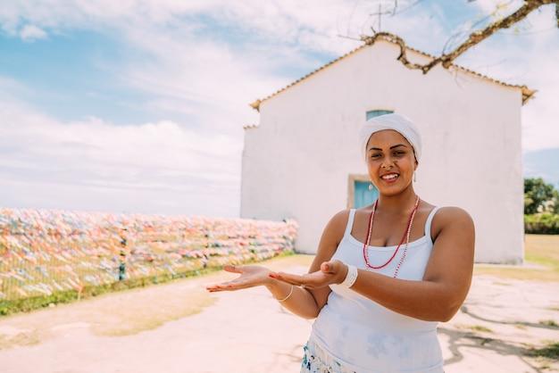 彼女の手のひらの上で何かを示す伝統的なバイーアの衣装を着た幸せなブラジル人女性は、背景にポルトセグロの歴史的中心部でカメラを見て