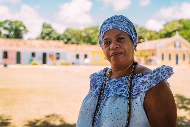 Happy brazilian woman dressed in the traditional bahian costume of the umbanda religion, in the historic center of porto seguro