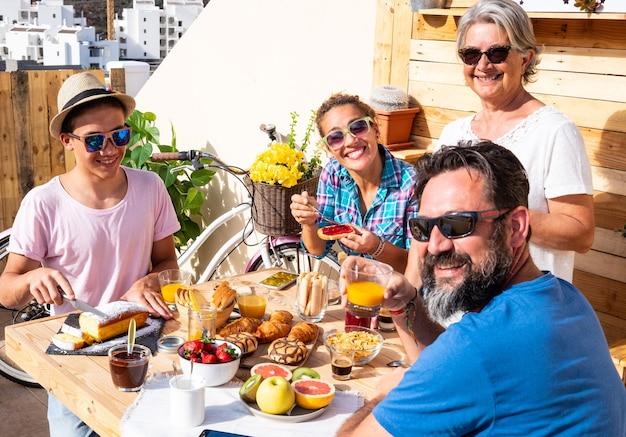 白人の家族のための幸せな朝食。テラスで屋外。健康的な食事。新鮮なフルーツとコーヒー。四人