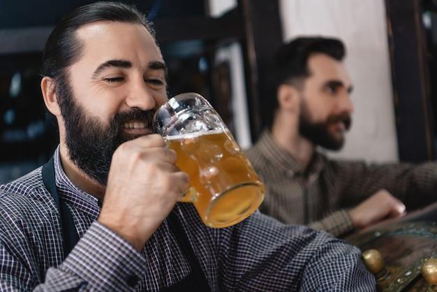 Happy brewer tastes craft ale beer manufacturing.