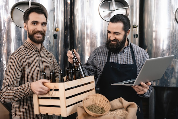 Happy brewers inspecting beer bottles at factory.