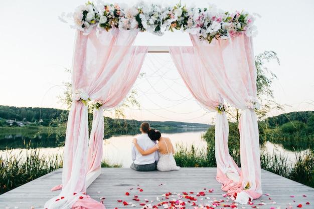 バラの花びらと結婚式のアーチの木製の場所に座って式後幸せな新郎新婦。湖の近くの日没で抱きしめる恋人のカップル。肩に頭。ロマンチック。