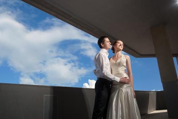 街の青い空の前で結婚式の散歩で幸せな新郎新婦