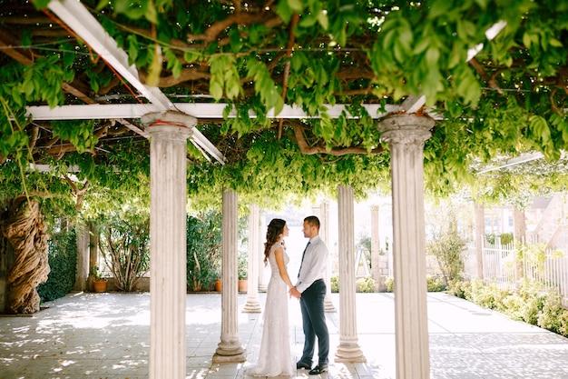 Счастливые жених и невеста, взявшись за руки, стоят между колоннами в красивом зеленом саду в солнечный день