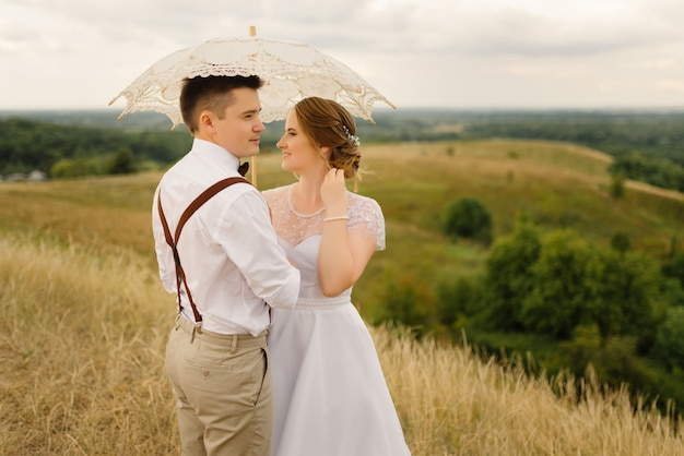 幸せな新郎新婦はお互いを抱きしめ、自然にヴィンテージの傘を差します。閉じる。結婚式、愛の概念。