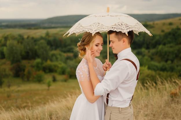 幸せな新郎新婦はお互いを抱きしめ、自然にヴィンテージの傘を差します。結婚式、愛の概念。