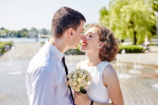 Счастливая невеста и жених обнимаются в парке