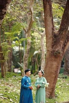 결혼식을 마친 후 공원에서 이야기하는 베트남 전통 의상을 입은 행복한 신부와 신랑