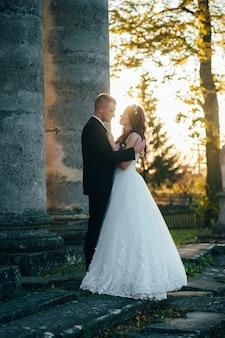 幸せな結婚式の日に中世の宮殿の近くの新郎新婦